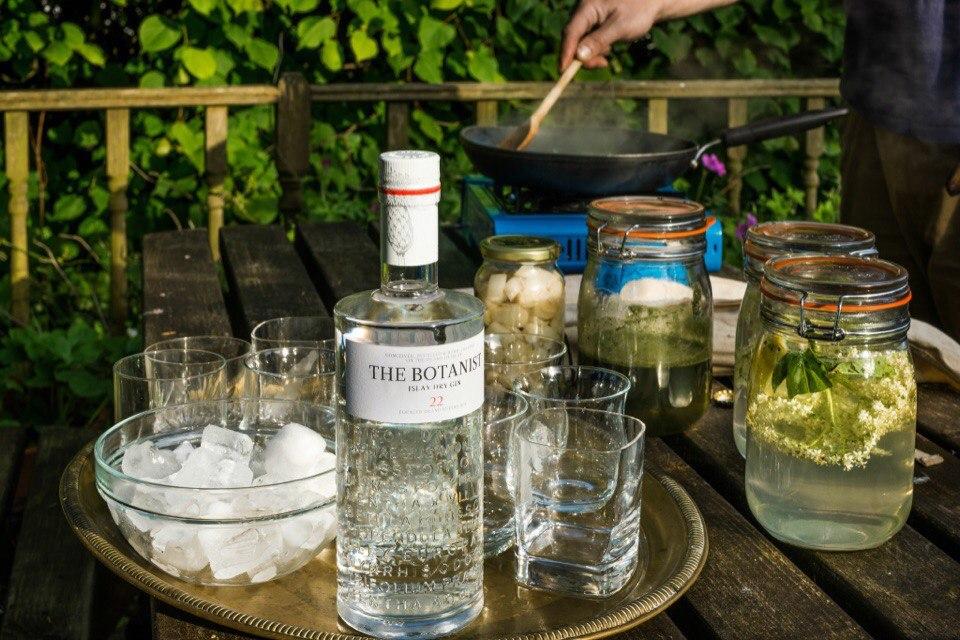 бутылка джина The Botanist на столе с бокалами со льдом и банками с настоями и специями