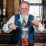 старый бармен делает коктейль борода седая смесительный стакан барный инвентарь