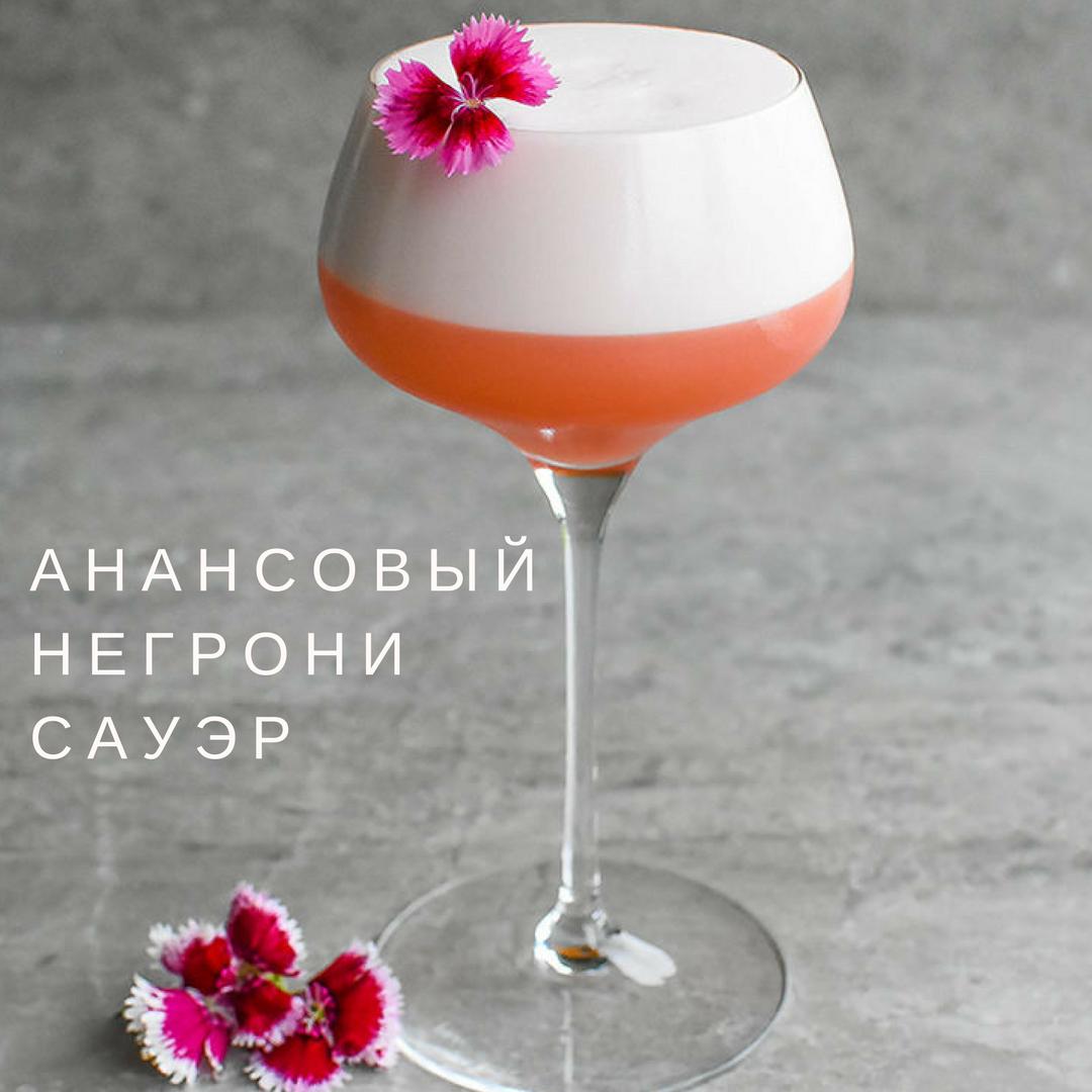 ананасовый негрони сауэр коктейль с цветком в крсивом бокале на длинной тонкой ножке рюмка на бетонном столе