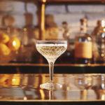 коктейль бокал шампанского игристого вина просекко на барной стойке купэ купе на фоне бутылок и барного инвентаря