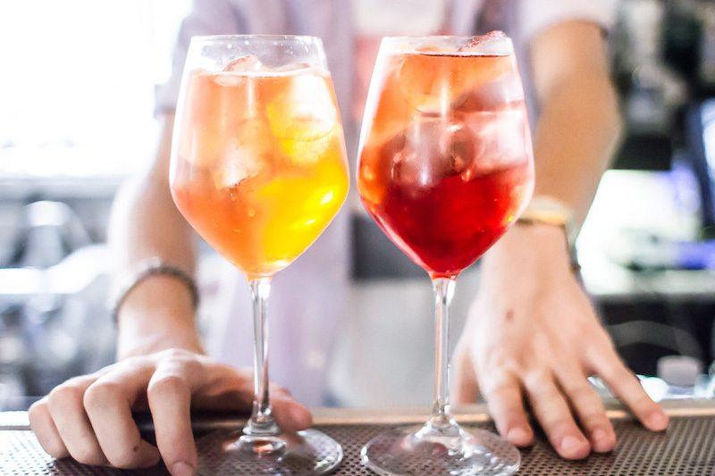 винные бокалы с двумя коктейлями - напиток жёлтого и рубинового красного цвета на барной стойке подача со льдом от бармена
