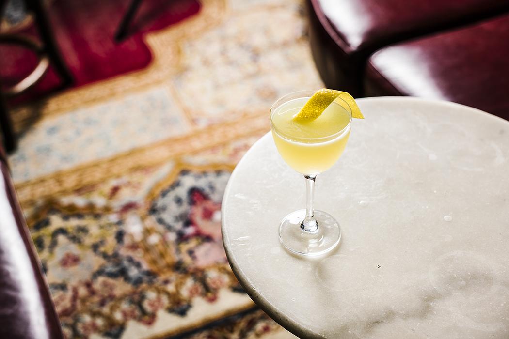 белый негрони дайкири твист на коктейль напиток настоле на фоне ковра с украшением из лимонной кожуры