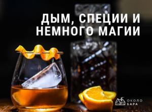 коктейль с цитрусом украшенный апельсиновой цедрой на шпажке на фоне графина декантера