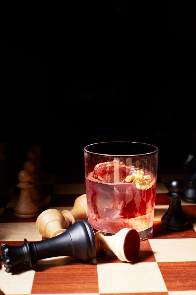 коктейль на шахматной доске разбросанные фигуры король лежит рядом с напитком