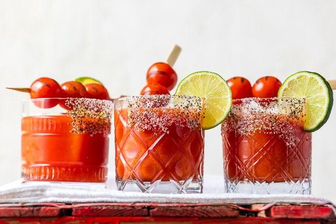 Коктейли Маргарита, украшенные томатами-черри, лаймами и крастой с одной стороны бокала