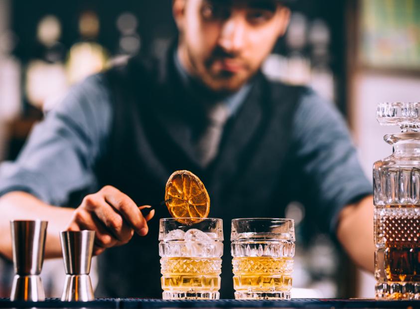 бармен кладёт апельсиновый чипс в два коктейля, стоящие на красивой коричневой барной стойке из дерева