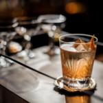 красивый коктейль на деревянном столе или столешнице коричневого цвета, украшенный апельсиновой цедрой