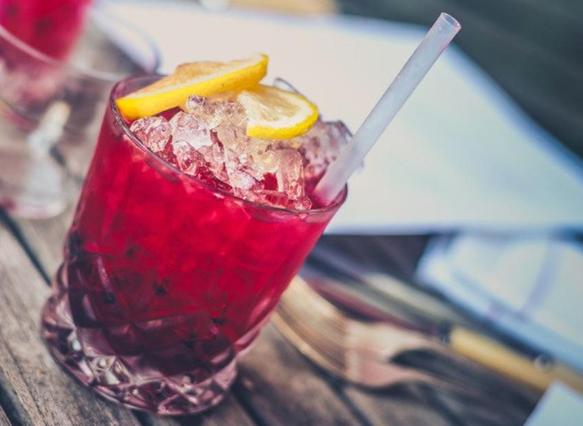 красный коктейль в бокале рокс или олдфешн с трубочкой и порезанными ломтиками слайсами лимонов и трубочкой на коричневом деревянном столе