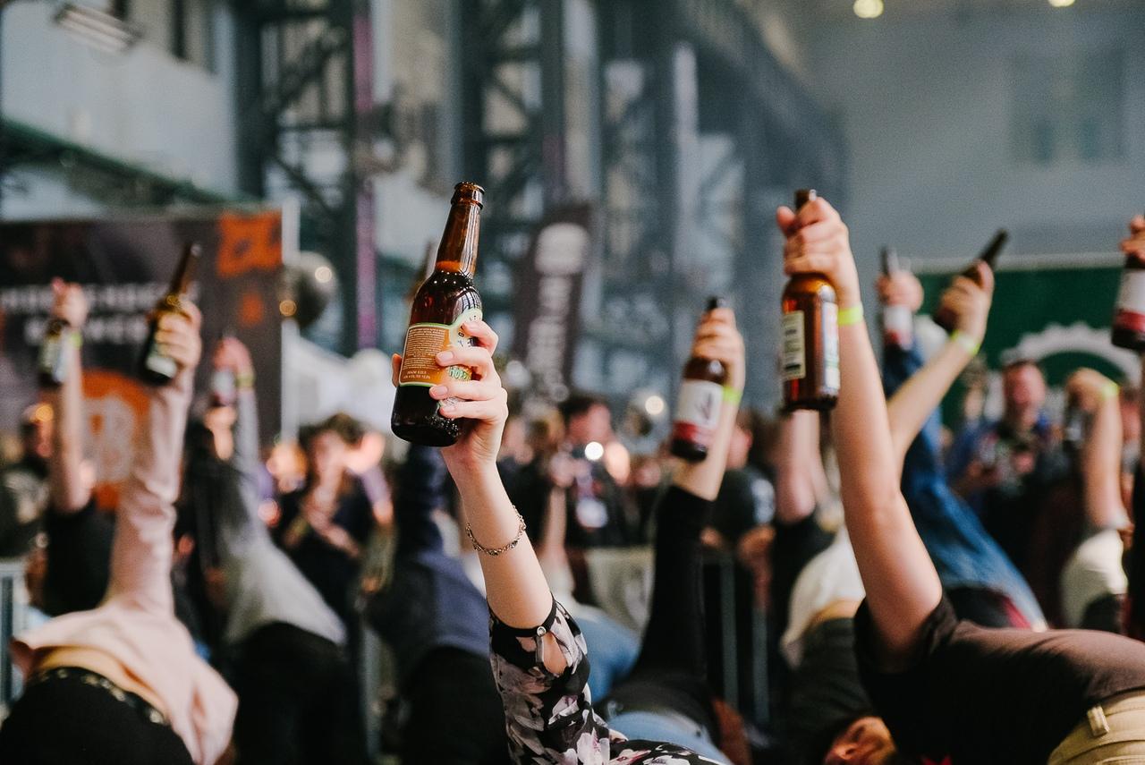 пивные бутылки поднятые в руке над головами в толпе крафтовый фестиваль