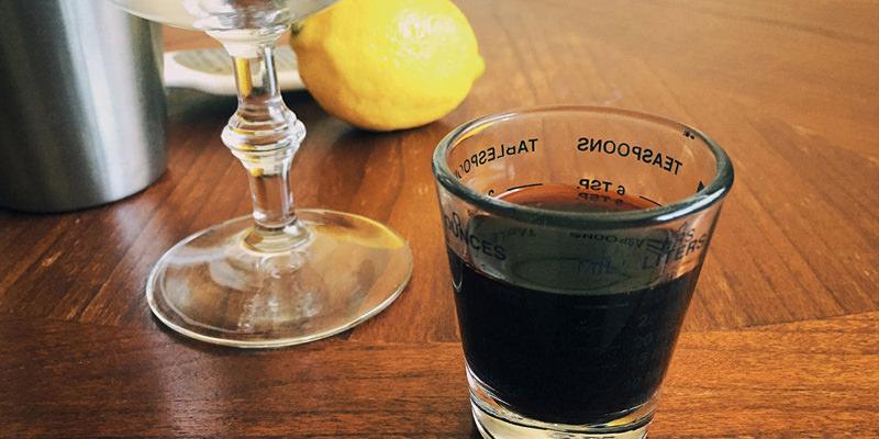мерный стаканчик тёмная жидкость бутылка биттер Ангостура Angostura bitter рядом с бокалом рецепт коктейля горечь в напитке