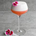 ананасовый негрони сауэр коктейль в бокале с пышной пенкой и украшенный цветком розового фиолетового цвета рюмка на тонкой ножке