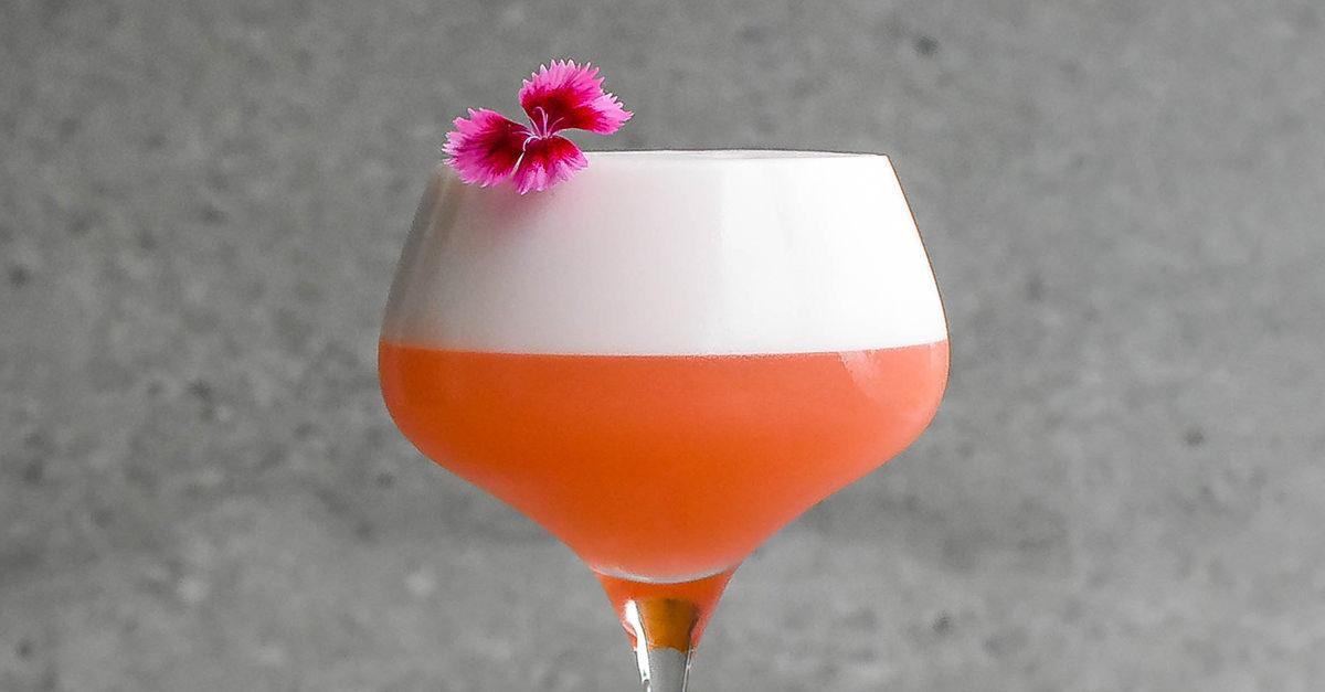 ананасовый негрони сауэр коктейль в бокале с пышной пенкой и украшенный цветком розового фиолетового цвета