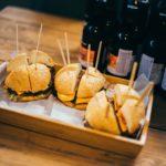 разрезанные бургеры на фестивале крафтового пива в питере рядом с бутылками на подносе