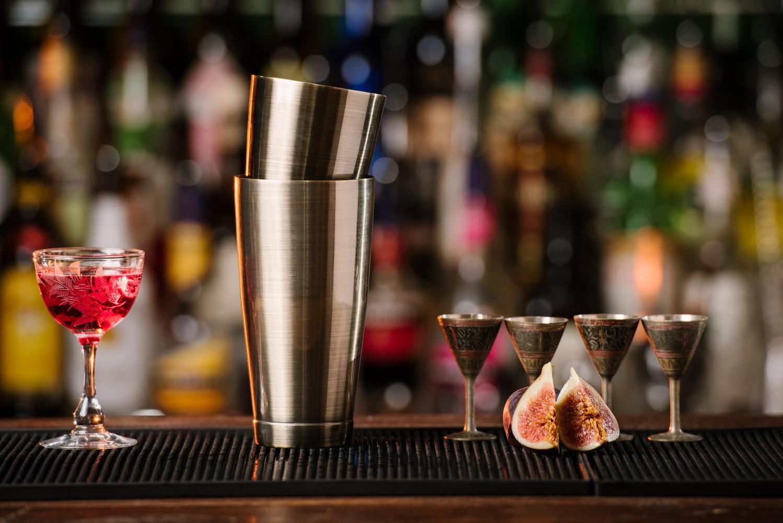шейкер бостон бостонский рядом с тремя коктейльными рюмками на барной стойке гайд как пользоваться шейкером