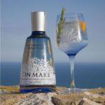 Джин Gin Mare бутылка и стакан с коктейлем на берегу обрыва