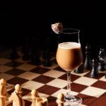 коктейль и шахматная доска фигуры рядом с напитком красивая необычная подача смешанного напитка