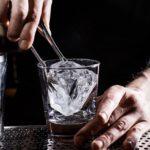 Бармен кладет лёд в бокал