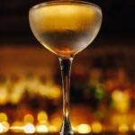 Carte Blanche (Берлин бар) коктейль жёлтого цвета на фоне боке в бокале шале на длинной тонкой ножке