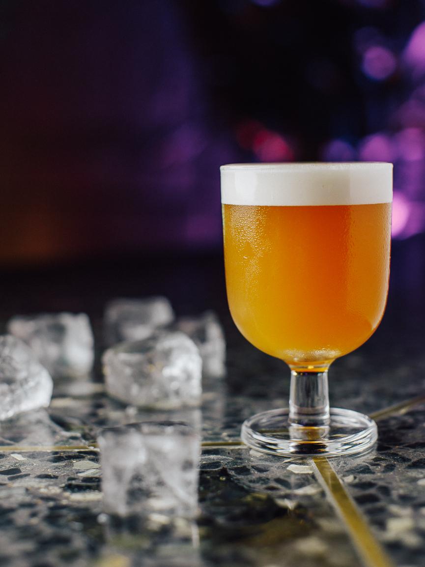 Коктейль Prime Minister 1 (Берлин бар) жёлтый коктейль в красивом бокале на ножке на барной стойке рядом с рассыпанным льдом