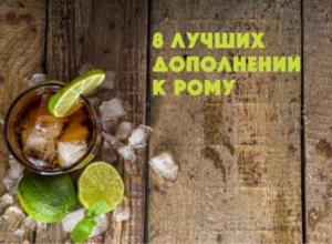 стакан с коктейлем куба либре ром кола стоит на деревянном досчатом столе коричневого цвета в углу фотографии с лаймом и льдом